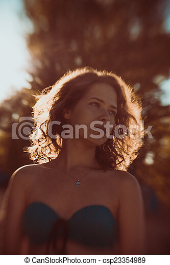 Beautiful face of the young sexy woman posing near the green tree on nature - csp23354989