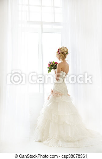 Beautiful fashion model. Sensual bride. Woman with wedding dress, hair and make up. Waiting for groom on background of window Blue eyes. Natural manicure. Beauty spring girl with bouquet of flowers in hands - csp38078361