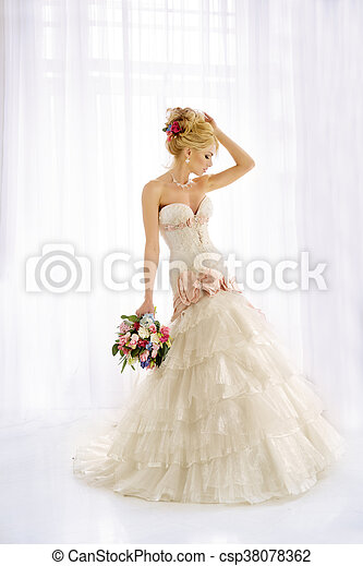 Beautiful fashion model. Sensual bride. Woman with wedding dress, hair and make up. Waiting for groom on background of window Blue eyes. Natural manicure. Beauty spring girl with bouquet of flowers in hands - csp38078362