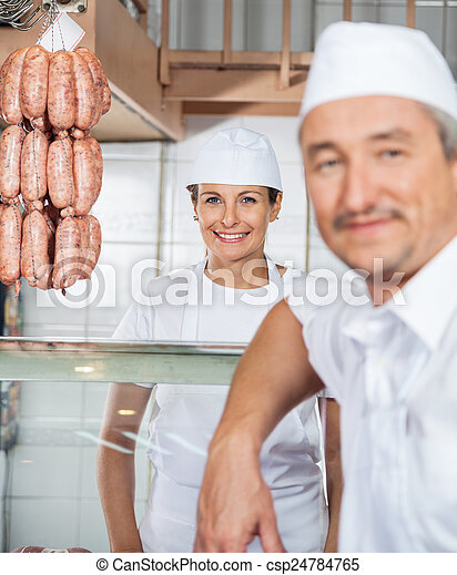 Beautiful Female Butcher With Colleague In Butchery - csp24784765