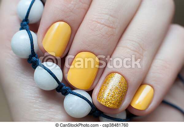 Beautiful Female Hand With Yellow Nail Design Close Up