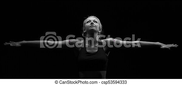 Beautiful fit and healthy blond woman in black top in dark with arms stretched artistic conversion - csp53594333