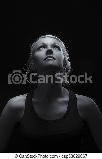Beautiful fit and healthy blond woman portrait in black top in dark with selective lighting artistic conversion - csp53629067
