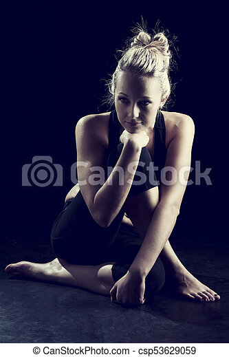 Beautiful fit and healthy blond woman portrait in black top crouch on floor artistic conversion - csp53629059
