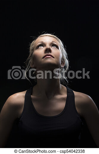 Beautiful fit and healthy blond woman portrait in black top in dark with selective lighting - csp54042338
