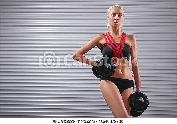65140de1 Beautiful fit young sportswoman exercising with dumbbells ...