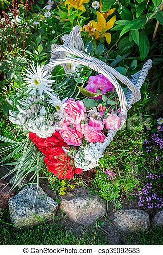Beautiful flowers in basket in sunny garden.