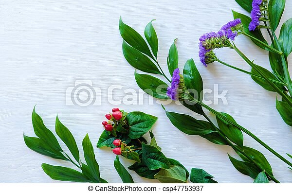 Beautiful flowers of lavender and red berries on white wooden background - csp47753937