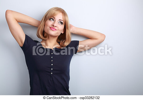 Beautiful fun thinking blond young woman in looking up on blue background - csp33282132