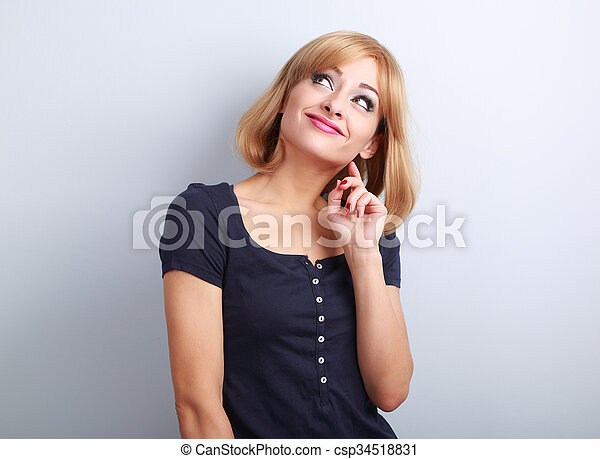 Beautiful funny thinking grimacing young woman looking up on blue background - csp34518831