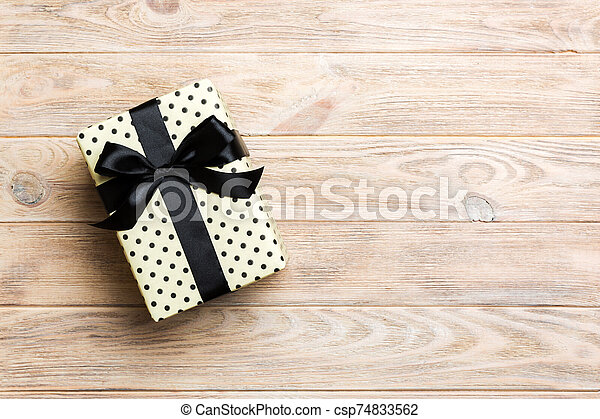 Beautiful gift box with a black bow on the yellow wooden table. Top view banner with copy space for you design - csp74833562