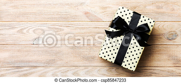 Beautiful gift box with a black bow on the yellow wooden table. Top view banner with copy space for you design - csp85847233