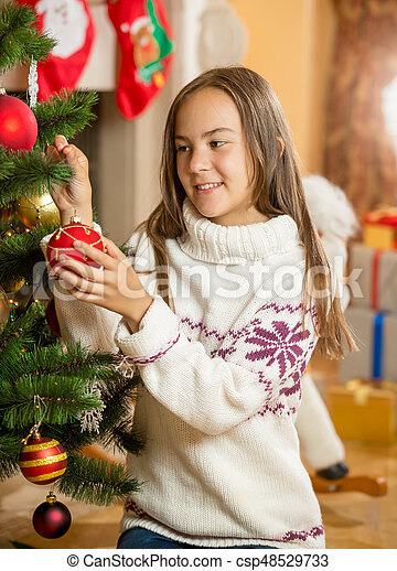 Beautiful girl decorating Christmas tree at living room