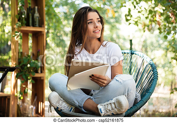 Beautiful girl holding a textbook while sitting in a chair - csp52161875