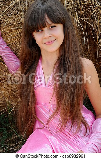 Beautiful girl in a field on a background of straw - csp6932961