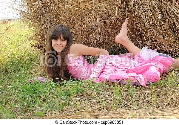 Beautiful girl in a field on a background of straw - csp6963851