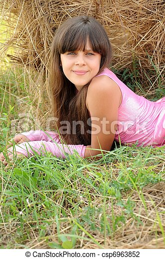 Beautiful girl in a field on a background of straw - csp6963852