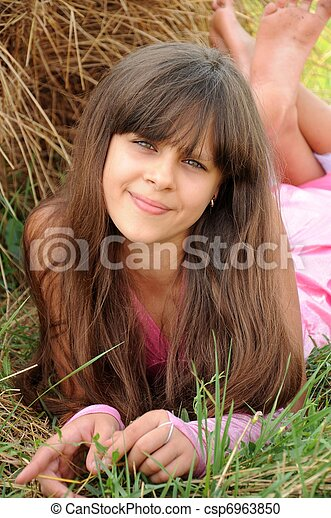 Beautiful girl in a field on a background of straw - csp6963850