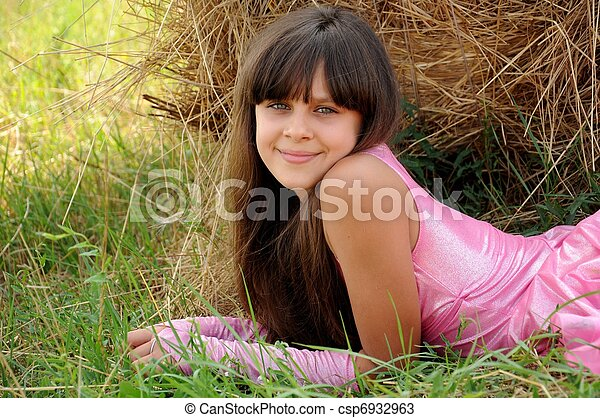 Beautiful girl in a field on a background of straw - csp6932963