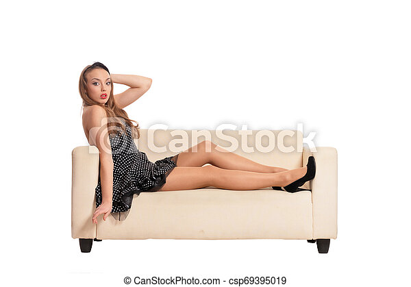 Beautiful girl in black dress posing on sofa isolated on white background - csp69395019