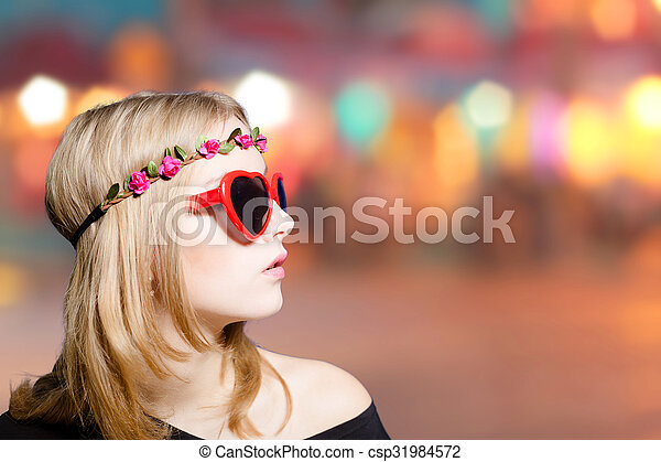 Beautiful girl in heart shaped sunglasses on bokeh background - csp31984572