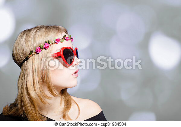 Beautiful girl in heart shaped sunglasses on bokeh background - csp31984504