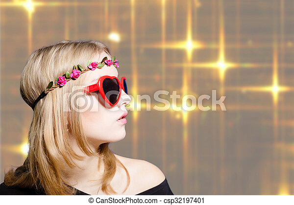 Beautiful girl in heart shaped sunglasses on bokeh background - csp32197401