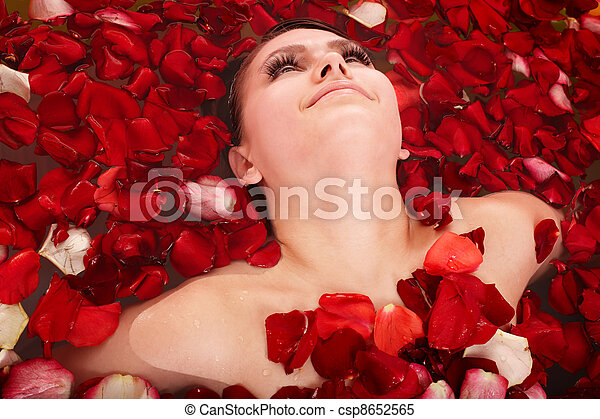 Beautiful girl in jacuzzi with rose petal. - csp8652565