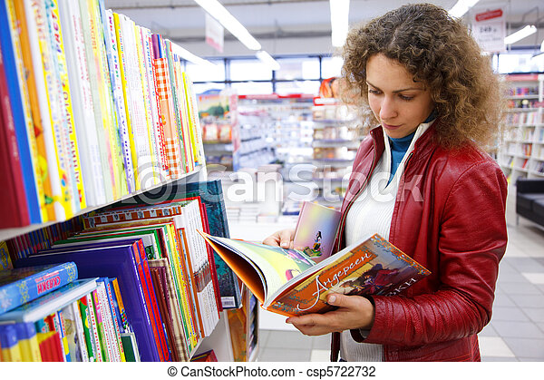 Beautiful girl in red jacket thoughtfully considers children's book in bookshop. - csp5722732