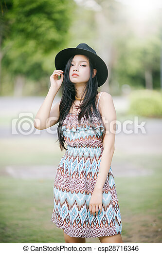 Beautiful girl is posing in vintage suit with black hat - csp28716346