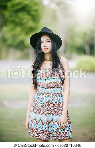 Beautiful girl is posing in vintage suit with black hat - csp28716348