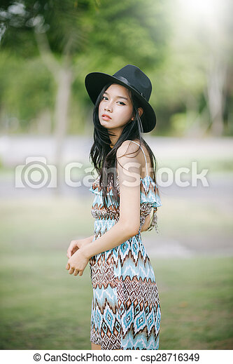 Beautiful girl is posing in vintage suit with black hat - csp28716349