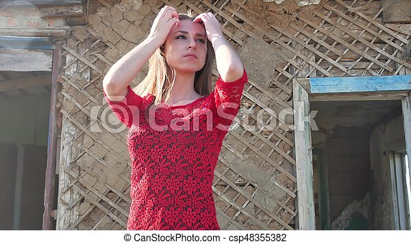 Beautiful girl lifestyle in a red dress. Sexy girl in a dress is standing next to the old house of the ruins - csp48355382