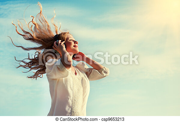 beautiful girl listening to music on headphones in the sky - csp9653213