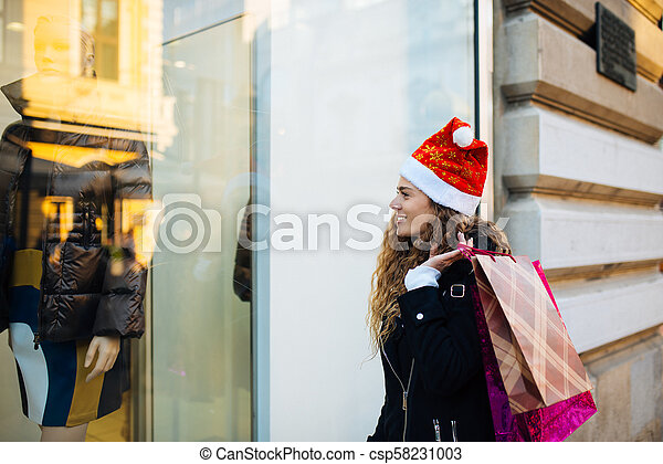 Beautiful girl looks at the shop window. - csp58231003