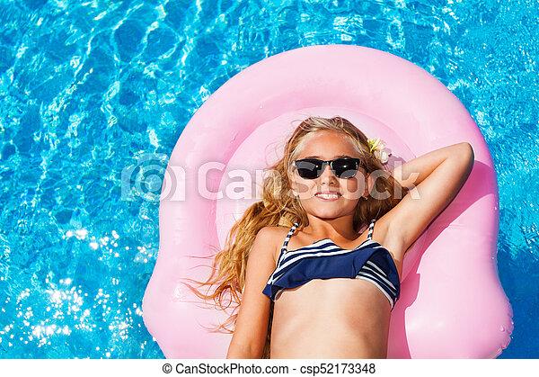 72292324c Beautiful girl on pink mattress in swimming pool. High-angle shoot ...