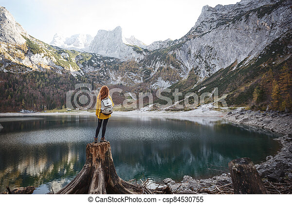 beautiful girl sitting on a stump - csp84530755