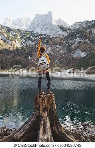 beautiful girl sitting on a stump - csp84530743