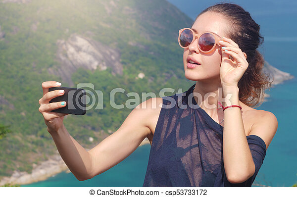 Beautiful girl traveler is taking a selfie with sea view at a height - csp53733172