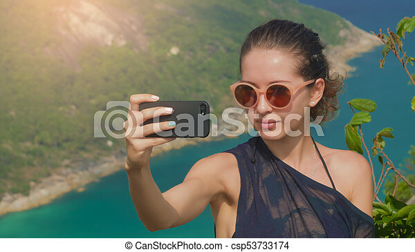 Beautiful girl traveler is taking a selfie with sea view at a height - csp53733174