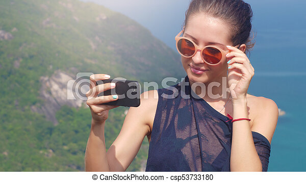 Beautiful girl traveler is taking a selfie with sea view at a height - csp53733180