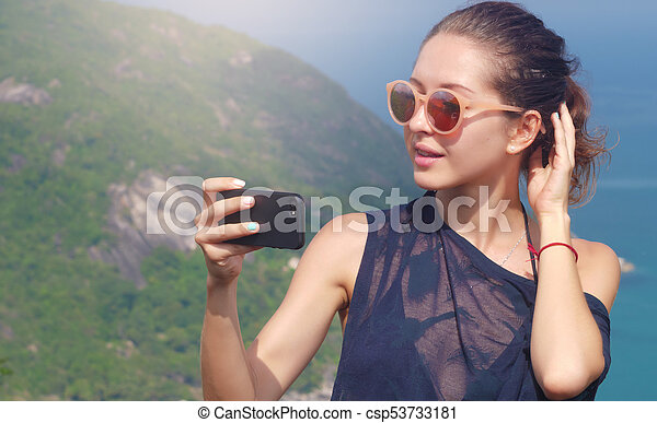 Beautiful girl traveler is taking a selfie with sea view at a height - csp53733181