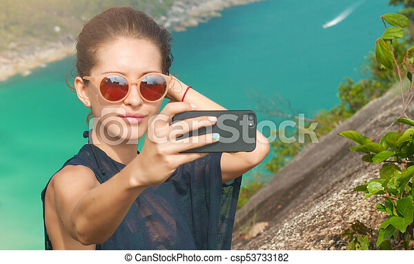 Beautiful girl traveler is taking a selfie with sea view at a height - csp53733182