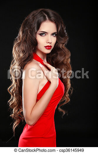 Beautiful girl with long wavy hair in red dress. Brunette with curly hairstyle posing isolaled on black background. - csp36145949
