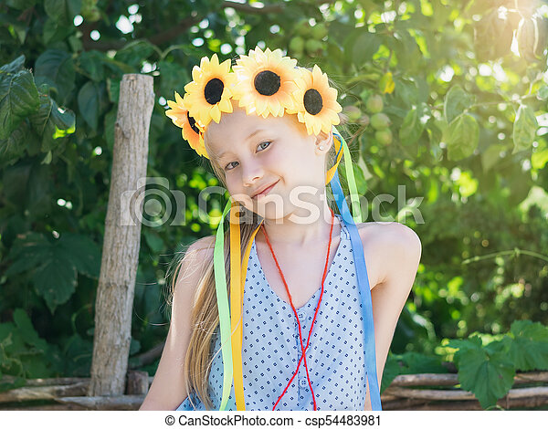 Beautiful girl with sunflowers on the head in the sunshine in front of the tree. - csp54483981