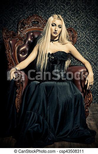 beautiful gothic woman with long blonde hair wearing black dress vintage interior castle style halloween