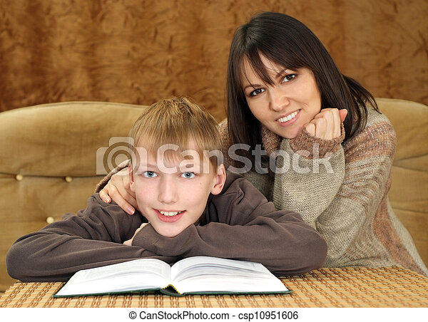 Beautiful happy Caucasian mother with her son reading a book - csp10951606