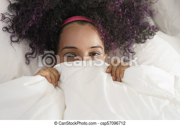 Beautiful Happy Hispanic Teen Waking Up And Smiling Undercover - csp57096712