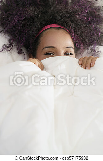 Beautiful Happy Hispanic Teen Waking Up And Smiling Undercover - csp57175932
