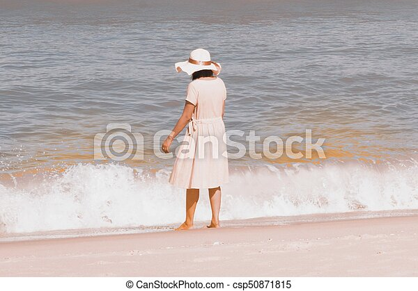 Beautiful happy multiracial Asian girl in vintage dresses standing on the beach. - csp50871815